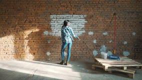 Построитель девушки на танцах и красках предпосылки кирпичной стены стена с белой краской видеоматериал