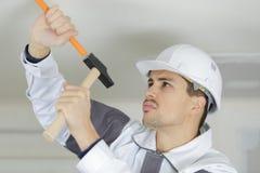 Построитель делая отверстие на потолке Стоковые Изображения