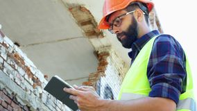Построитель инженера в шлеме высчитывает строя план разрушений и смотрит строительный проект на a акции видеоматериалы