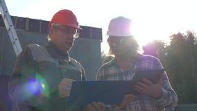 Построитель и дизайнер в шлеме обсуждают конструкцию согласно проекту плана видеоматериал