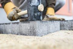Построитель утрамбовывая вниз новые вымощая сляб или кирпич Стоковая Фотография RF