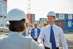 Построители делая рукопожатие на строительной площадке Стоковое фото RF