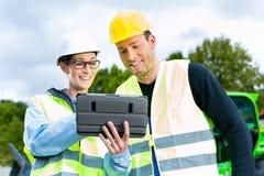 Построители с светокопией на строительной площадке Стоковая Фотография