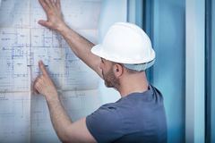 Построитель архитектора изучая план плана комнаты Стоковые Фото