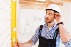 Построитель в защитном шлеме с доской сзажимом для бумаги и карандашем внутри помещения Стоковая Фотография RF