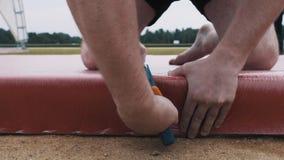 Построитель в шортах кладет красный материал на constructuion этапа используя сшиватель акции видеоматериалы