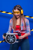 Построитель девушки в шлеме конструкции и изумлённые взгляды с инструментом конструкции на голубой предпосылке Стоковые Фотографии RF