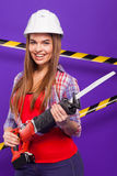 Построитель девушки в шлеме конструкции и изумлённые взгляды с инструментом конструкции на голубой предпосылке Стоковые Фото