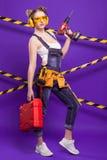 Построитель девушки в шлеме конструкции и изумлённые взгляды с инструментом конструкции на голубой предпосылке Стоковые Изображения RF
