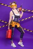 Построитель девушки в шлеме конструкции и изумлённые взгляды с инструментом конструкции на голубой предпосылке Стоковая Фотография