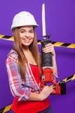 Построитель девушки в шлеме конструкции и изумлённые взгляды с инструментом конструкции на голубой предпосылке Стоковое Фото