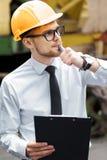 Построитель инженера в шлеме держит папку на строительной площадке Стоковые Изображения RF