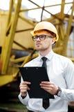 Построитель инженера в шлеме держит папку на строительной площадке Стоковая Фотография