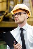 Построитель инженера в шлеме держит папку на строительной площадке Стоковые Фотографии RF