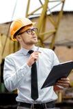 Построитель инженера в шлеме держит папку на строительной площадке Стоковое Изображение RF
