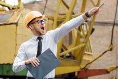 Построитель инженера в шлеме держит чертежи и показывает вручную на строительной площадке Стоковое Изображение RF