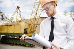 Построитель инженера в шлеме держит чертежи на строительной площадке Стоковые Фотографии RF