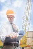 Построитель инженера в шлеме держит чертежи на строительной площадке Стоковое фото RF