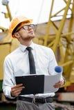 Построитель инженера в шлеме держит чертежи на строительной площадке Стоковое Фото