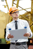 Построитель инженера в шлеме держит чертежи на строительной площадке Стоковая Фотография