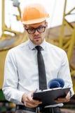 Построитель инженера в шлеме держит чертежи на строительной площадке Стоковая Фотография RF
