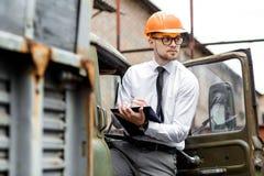 Построитель инженера в шлеме держит чертежи на строительной площадке Стоковое Изображение