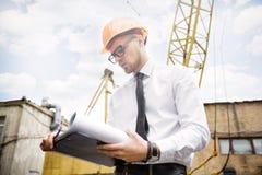 Построитель инженера в шлеме держит чертежи на строительной площадке Стоковые Фото