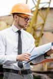 Построитель инженера в шлеме держит чертежи на строительной площадке Стоковые Изображения RF