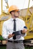 Построитель инженера в шлеме держит чертежи на строительной площадке Стоковые Изображения