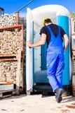 Построитель используя передвижной туалет на месте Стоковое Фото