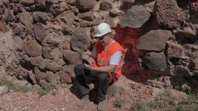 Построитель используя таблетку около стены каменного замка видеоматериал