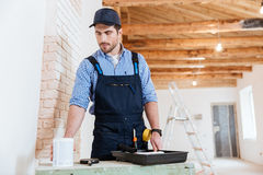 Построитель идя покрасить стены внутри помещения Стоковые Фото
