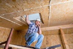 Построитель на сотовом телефоне внутри незаконченного дома Стоковое Изображение RF