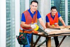 Построитель пиля деревянную доску здания или строительной площадки Стоковые Фото