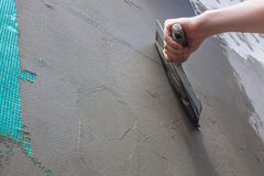 Построитель положил миномет на стену Стены гипсолита Стоковое Изображение
