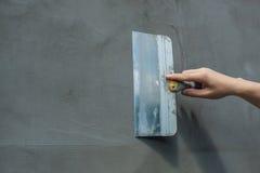 Построитель положил миномет на стену Стены гипсолита Стоковые Фото