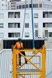 Построитель собирает кран башни конструкции Стоковые Фото