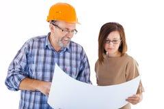 Построитель старшего человека и молодой инженер смотря проект Стоковые Фото