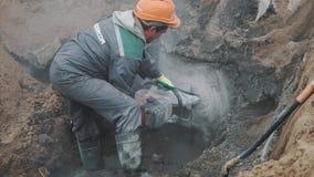 Построитель с бетонной конструкцией вырезывания круглой пилы в канаве на строительной площадке сток-видео