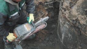 Построитель с бетонной конструкцией вырезывания круглой пилы в рве на строительной площадке видеоматериал