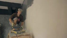 Построитель тщательно красит стену в сером цвете используя специальный ролик видеоматериал