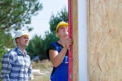 2 построителя устанавливая изолированные панели стены Стоковая Фотография RF