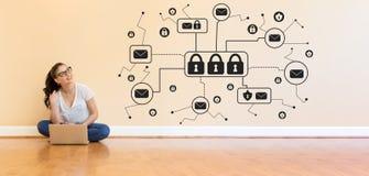 Посылайте тему по электронной почте безопасностью при молодая женщина используя портативный компьютер стоковая фотография