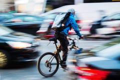 Посыльный велосипеда в занятом городском транспорте Стоковые Изображения