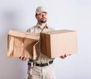 Посыльный держа нормальные и сломленные пакеты, белую предпосылку стоковое фото rf