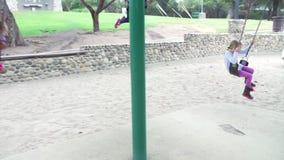 Последовательность замедленного движения 4 маленьких девочек играя на качаниях акции видеоматериалы