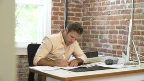 Последовательность промежутка времени бизнесмена работая на столе в офисе видеоматериал