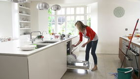 Последовательность промежутка времени занятой женщины работая в кухне акции видеоматериалы
