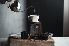 Потек кофе, рука держа кофе потека чайника в комнате Стоковое Фото