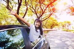 Потеряйте вверх по стороне азиатской эмоции счастья подростка в личном автомобиле против зеленой окружающей среды городской улицы стоковые фото